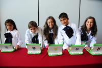Nenas y nenes con un ordenador portátil proporcionado por el Plan Ceibal.